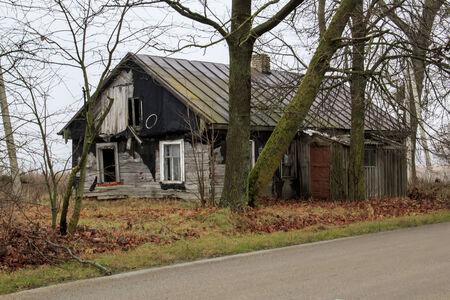 bombed city: Ruinous farmhouse among autumn leaves Stock Photo