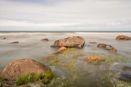 dry grass: stones in sea Stock Photo