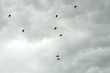 parachutists: Parachutists siluets in sky Stock Photo