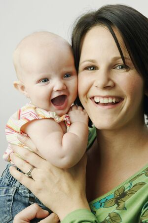 A mother is holding up her infant daughter and both are smiling for the camera. Vertical shot. Stock Photo
