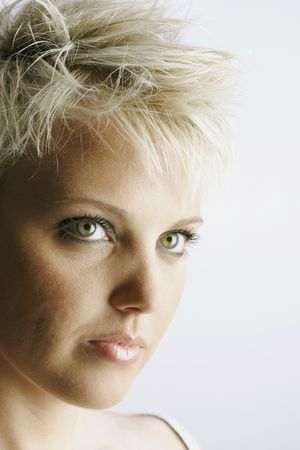 Portrait of an attractive young woman with short blonde hair and green eyes. Vertical shot.