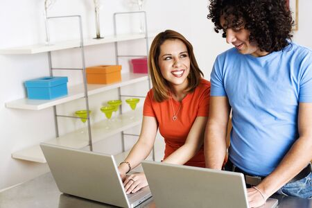 A young man and woman are smiling at one another while working side by side on laptops. Horizontal shot. Stock Photo