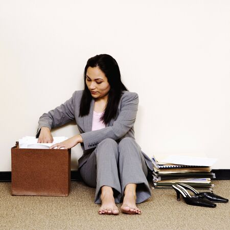 A young businesswoman is sitting on the floor with her shoes off and looking through a file folder. Square shot. photo