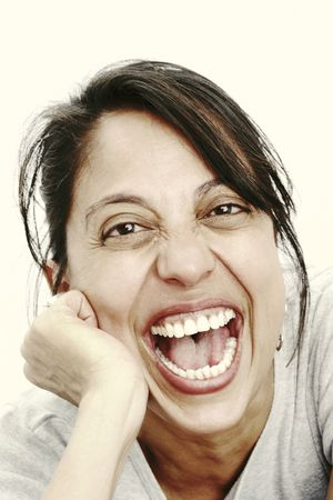 A middle-aged woman leans forward with her head resting on her hand and laughs. Vertical shot. Stock Photo