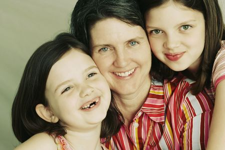A mother and her two young daughters embrace and smile towards the camera. Horizontal shot