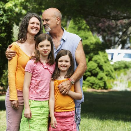 A couple affectionately stand with their two young daughters in their front yard. Square shot.