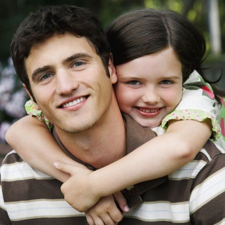 Young girl wraps her arms around a young man from behind. They are both smiling towards the camera. Square shot.