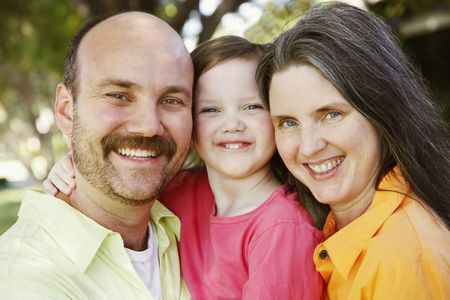 Mother and father hold their daughter between them as all three smile for the camera. Horizontal shot.