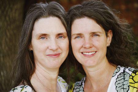 Two women stand cheek to cheek and smile towards the camera. Horizontal shot.