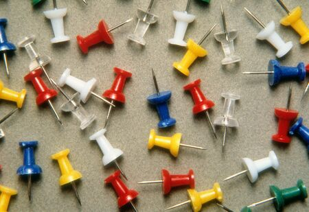 Different colors of pushpins scattered on a counter top. Horizontal shot.