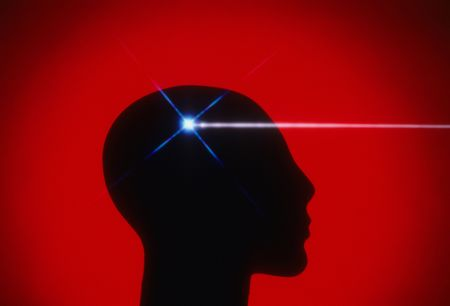 Profile of a mannequin head silhouetted against a red background, with a beam of white light coming from the brain region. Horizontal shot. Stock Photo - 6659491