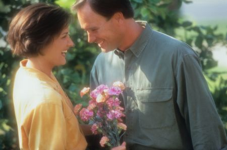 Side view of a man giving a woman a bouquet of flowers. Both are smiling, and there are trees in the background. Horizontal shot.