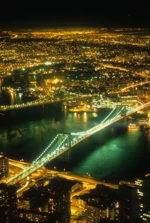 Aerial of the Manhattan and Brooklyn Bridges at night with the city lights in the background. Vertical shot. Stock Photo