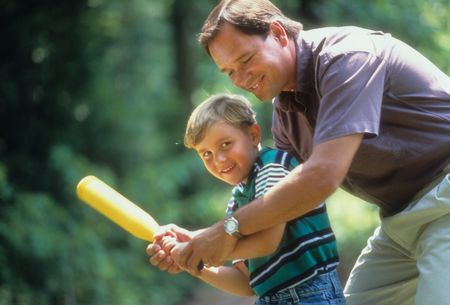 Cropped image of a father showing his young son how to hold and swing a plastic baseball bat.  Both are smiling. Horizontal shot.