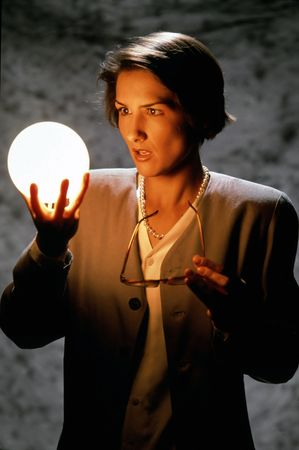 A businesswoman holding eyeglasses and a glowing ball and staring intently at the ball. Vertical shot.