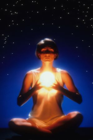 Front view of a woman meditating with crossed legs and eyes closed while holding a glowing ball.  She is sitting in front of a starry night-time background. Vertical format. Stock Photo