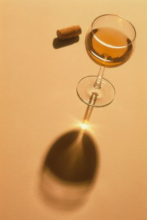 High angle view of a cork and a glass of wine.  Light is being magnified through the glass stem, causing a point of light on the shadow. Vertical shot Stock Photo