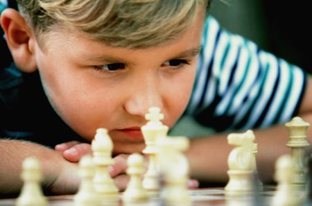 Cropped close-up of a young boy resting his head on his hands as he studies a chess board. Horizontal shot. Stock Photo