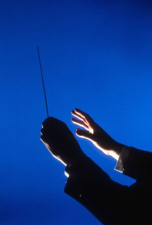 Hands of an orchestra conductor holding a baton against a blue background. Vertical shot.