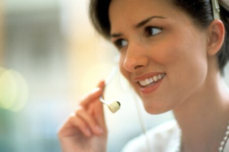 Cropped close-up of an attractive woman smiling while listening to a telephone headset. Horizontal shot.
