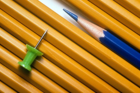 Standard pencils and a sharpened blue pencil are lined up next to each other.  There is a green pushpin on top of the pencils. Horizontal shot.