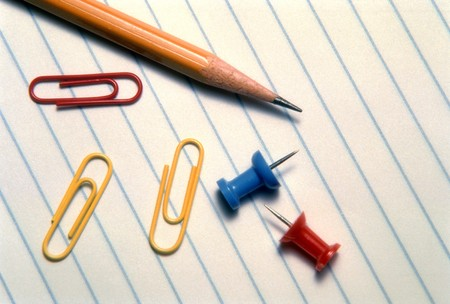 A pencil, paper clips and pushpins are lying on a piece of lined notebook paper. Horizontal shot.