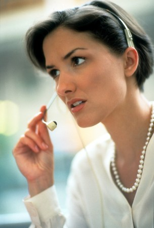 Cropped close-up of an attractive woman smiling while listening to a telephone headset. Vertical shot.