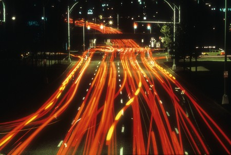 Tail lights of cars are seen at night as red lines as they pass along a street through an intersection. Horizontal shot. Stock Photo