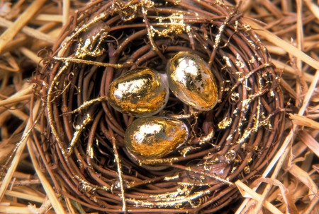 Overhead view of a woven nest sitting in straw with three golden eggs. Horizontal shot.