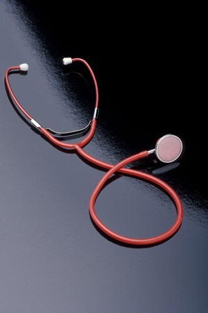 A red stethoscope is laying on a black reflective surface. Vertical shot.