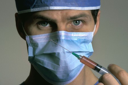 A male doctor is wearing a mask and holding a syringe with medicine in it. Horizontal shot. Stock Photo