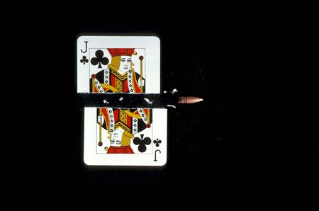 A jack of clubs is shown being shot in half by a bullet. Horizontal shot.