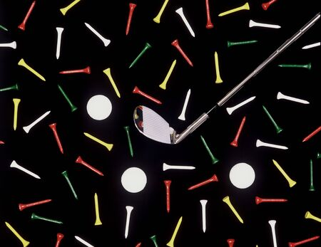 Golf club with balls and tees is shown in an overhead shot with a black background. Horizontal shot.