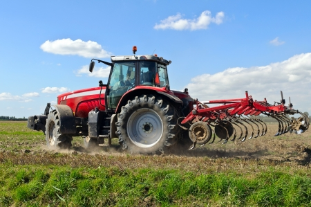 plowed field: red tractor during cultivation with plough