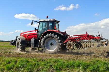 traktor: Roter Traktor mit Pflug w�hrend der Kultivierung