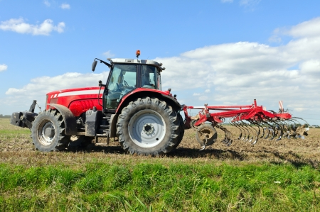 red tractor during cultivation with plough  Stock Photo - 14113923