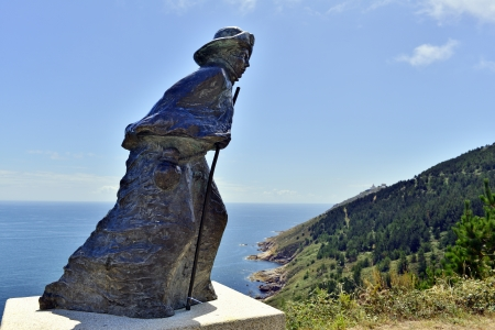 statue of a pilgrim at cape fisterra galicia spain photo