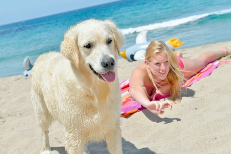 teenage girl with dog on the beach photo