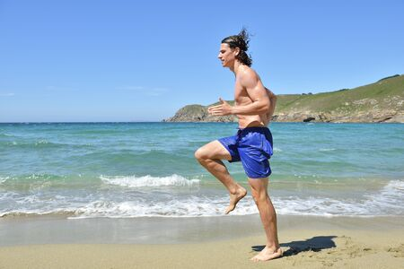 young sportsman running on the beach Stock Photo - 15393904