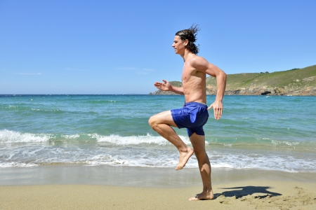 young sportsman running on the beach photo