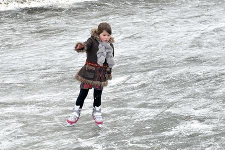 skates: little girl learning ice skating outdoors
