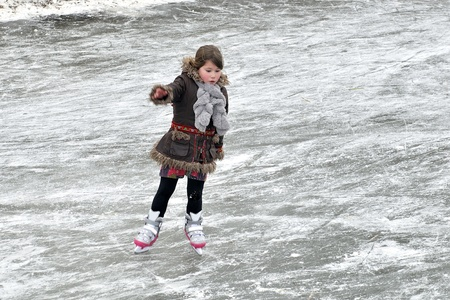 little girl learning ice skating outdoors