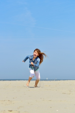 child playing and running on the beach  photo