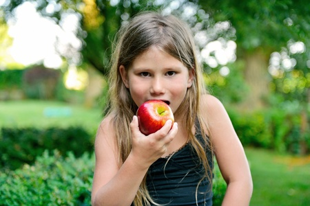 child eating a red apple with green garden as background Stock Photo - 21375500