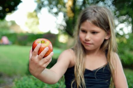 child eating a red apple with green garden as background  photo