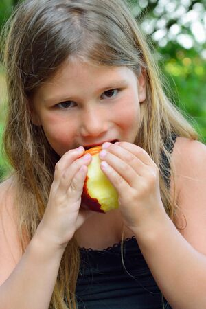 child eating a red apple with green garden as background  Stock Photo - 21375502