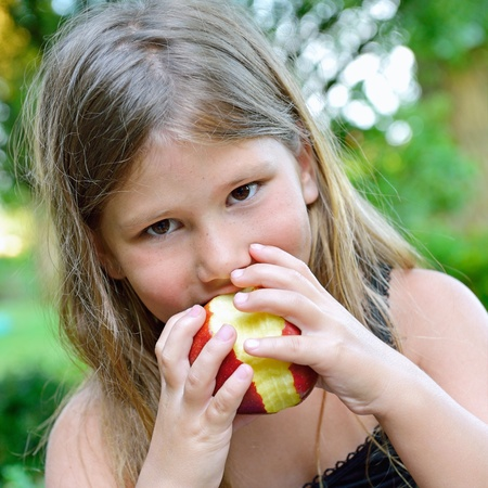 child eating a red apple with green garden as background  Stock Photo - 21375503