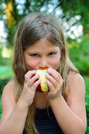 child eating a red apple with green garden as background  Stock Photo - 21375505