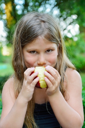 child eating a red apple with green garden as background  Stock Photo - 21375506