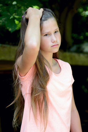sad young girl with long blond hair outside Stock Photo
